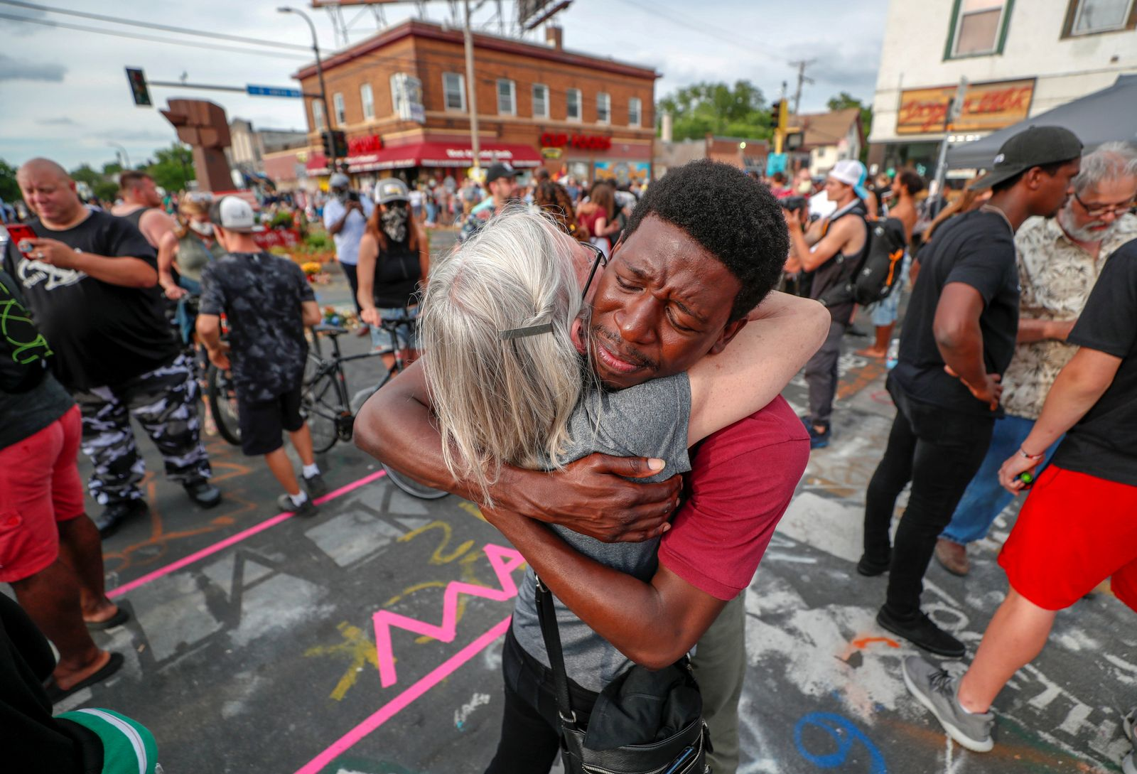 People hug during a Juneteenth observation in Minneapolis