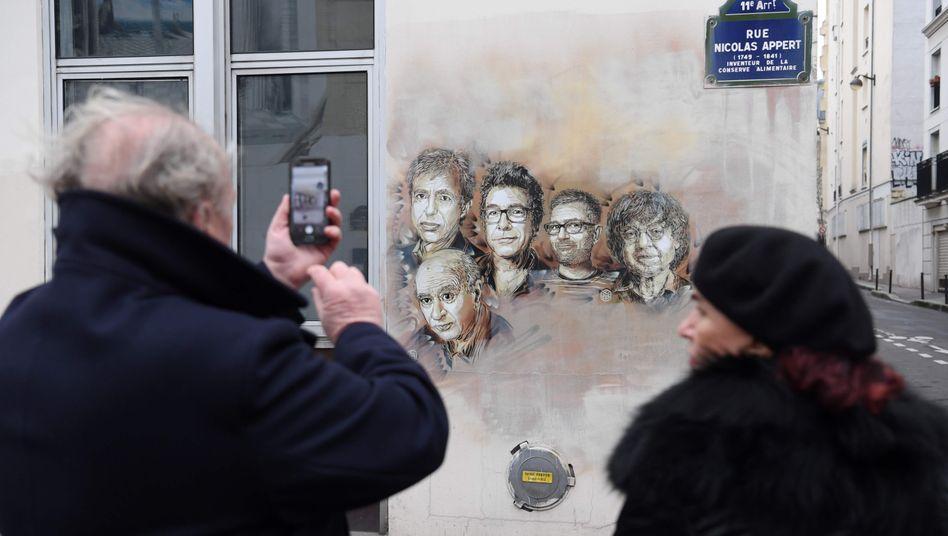 Passanten in der Nähe des Tatorts vor Porträts der Opfer