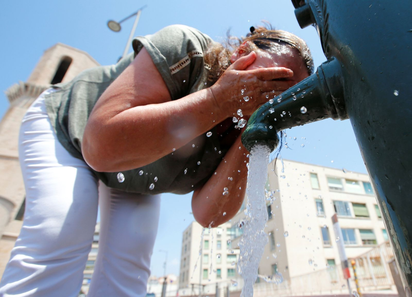 A woman cools off in a water fountain in Marseille as a heatwave hit much of the country