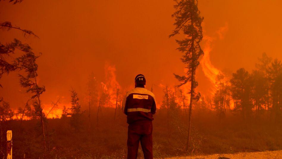 Ein Feuerwehrmann beobachtet die Brände im Osten Russlands