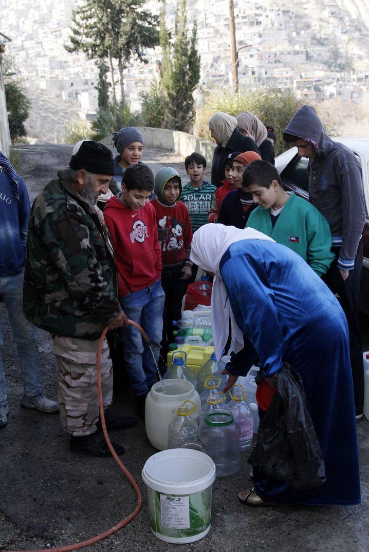 Syrer an Wasserstelle in Damaskus
