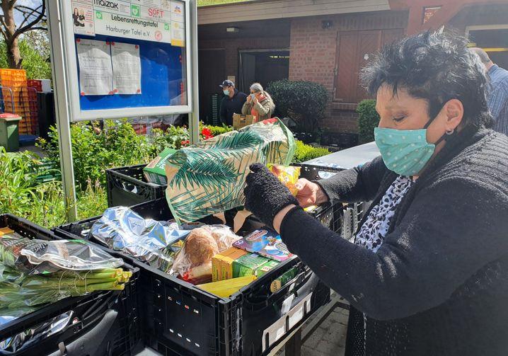 Eine Tafelkundin in Harburg begutachtet die Lebensmittel: Was sie nicht essen möchte, verschenkt sie
