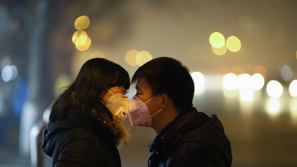 Chinesen mit Atemmasken in Peking: Weit jenseits des WHO-Werts