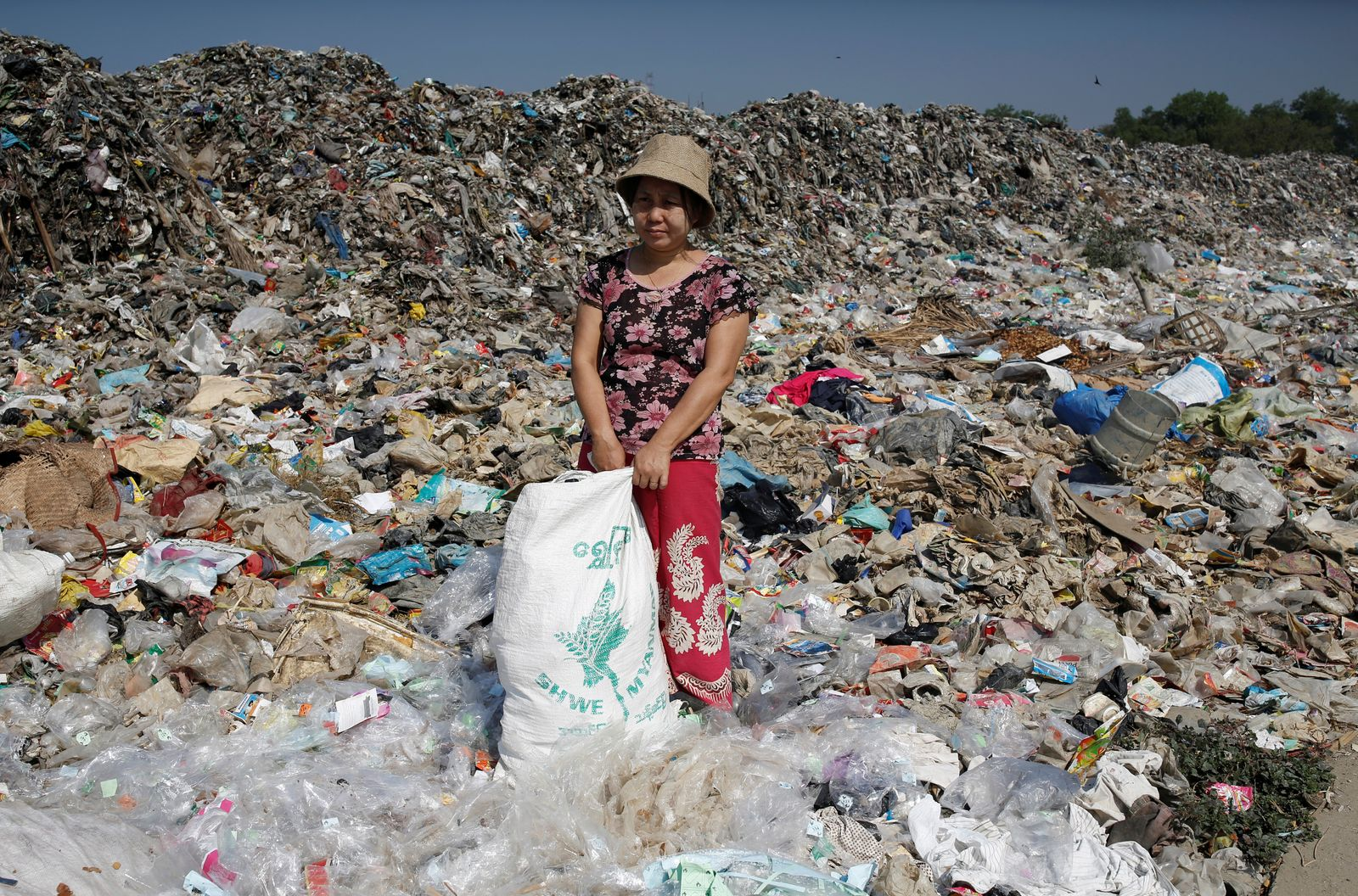 Hla Hla Nwe, a staff member of Chuchu House, takes a break from picking trash usable as materials to be turned into recycled products in Dalla township, Yangon