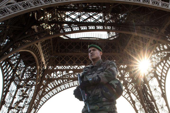 Bewaffneter Polizist unter dem Eiffelturm