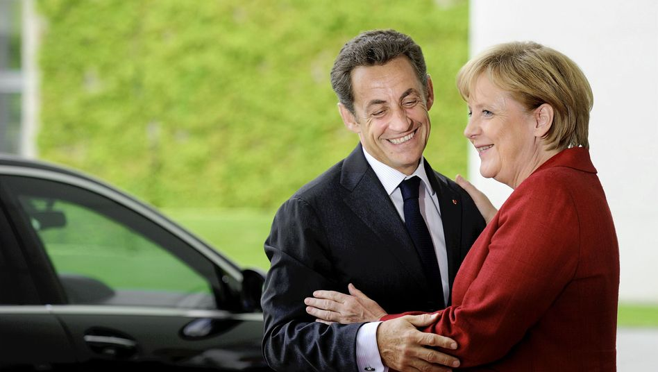 Merkel giving Sarkozy a warm welcome in Berlin on Monday.