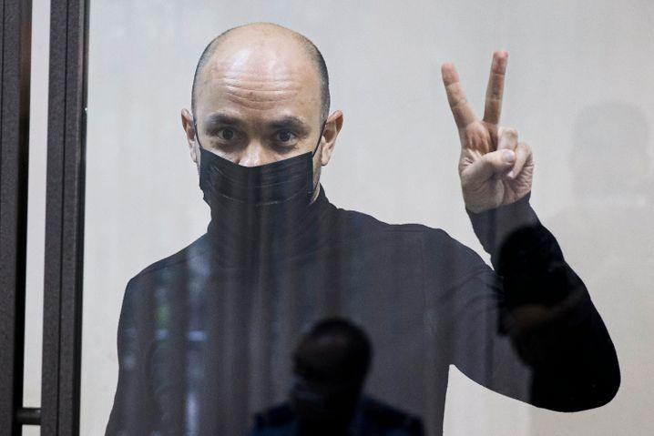 Andrej Piwowarow zeigt während einer Gerichtsverhandlung am 2. Juni hinter einer Glaswand das »Victory«-Zeichen