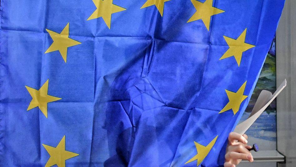Eine Frau verlässt mit einem Stimmzettel in der Hand eine Wahlkabine mit einer Europaflagge als Vorhang
