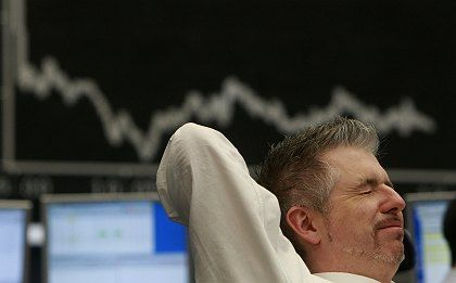 A trader reacts in front of the DAX board at the Frankfurt stock exchange.