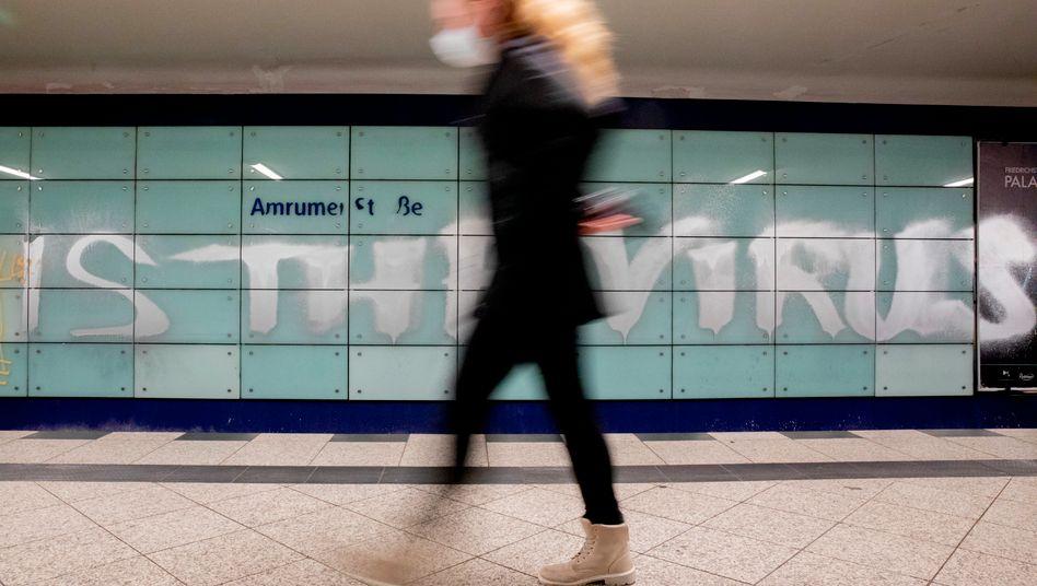 Nahverkehrsnutzerin in Berlin mit Mund-Nasen-Schutz vor einem Virusgraffiti
