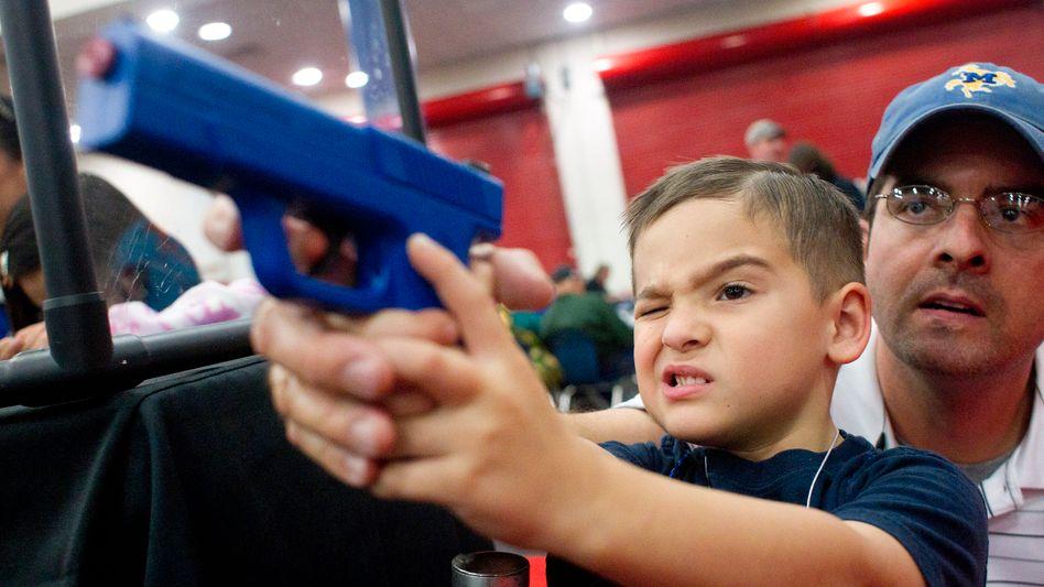 """Ein Vater gibt seinem Sohn bei einem Treffen der NRA Schützenhilfe: """"Freier Zugang zu Waffen, so wie wir freien Zugang zu Bildung haben"""""""
