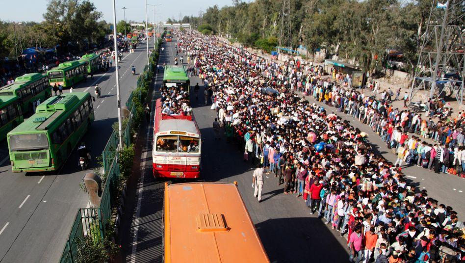 Viele Wanderarbeiter sind arbeitslos geworden, sie warten, wie hier in Delhi, auf einen Bus nach Hause.