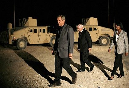 """US President George W. Bush (left) walks in front of Humvees with Defense Secretary Robert Gates and Secretary of State Condoleezza Rice: """"We are coming to prepare the field for you politicians."""""""