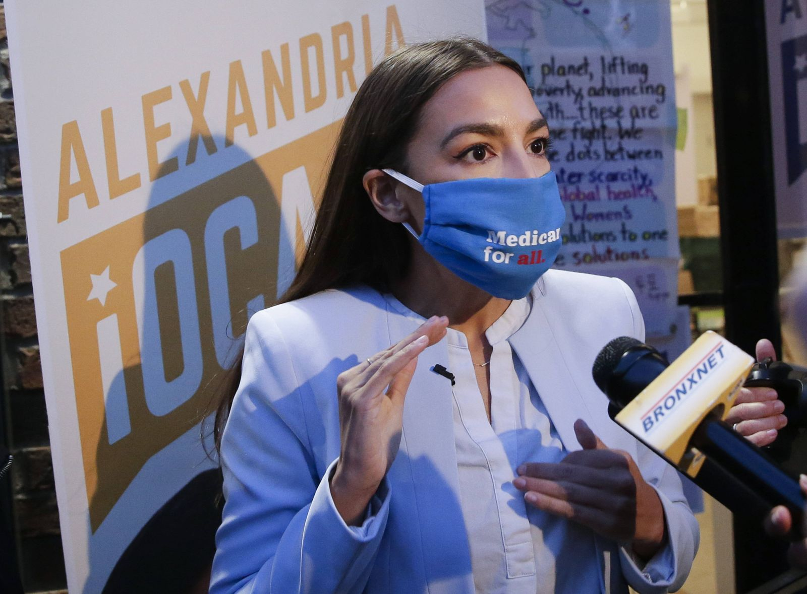Congresswoman Alexandria Ocasio-Cortez speaks to the press after she thanks her campaign team with a rally outside of h