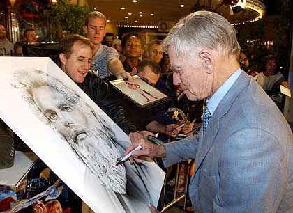 Darsteller Heston (beim Signieren eines Porträts, das ihn als Moses zeigt): Auf zur Heldenzertrümmerung