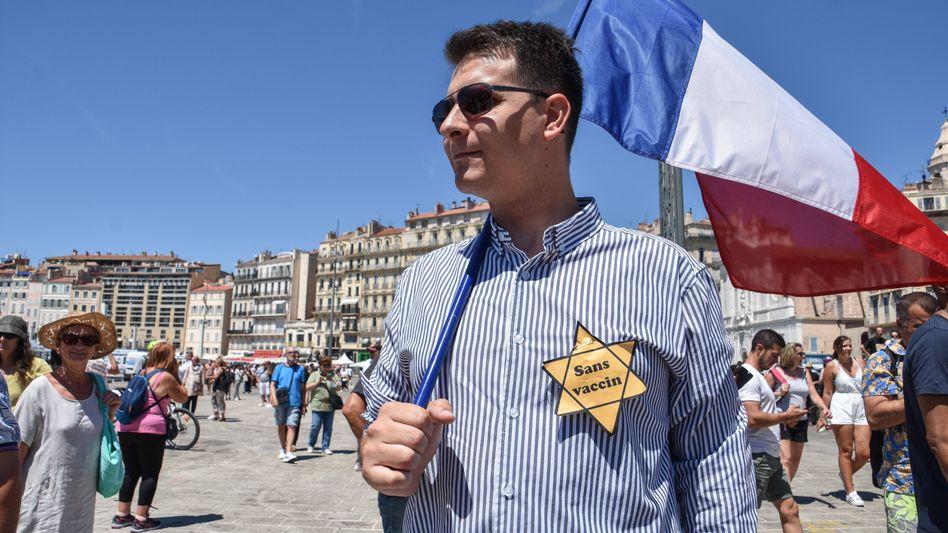 Corona-Protest in Marseille – mit Flagge und gelbem Stern, eine Anspielung an den sogenannten Judenstern während der NS-Zeit