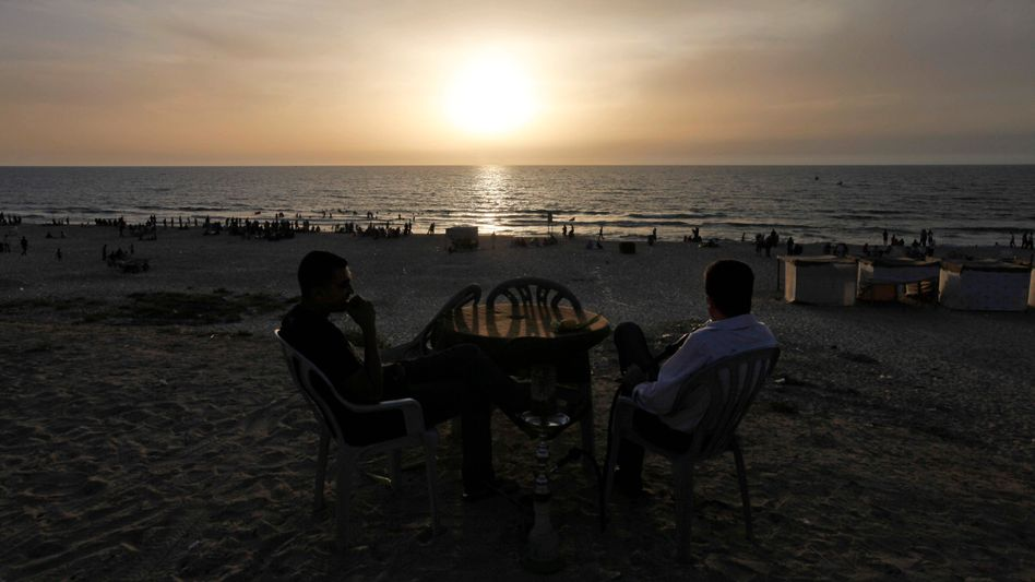 Palestinians enjoying a water pipe while looking out into the Mediterranean Sea. The waters off the Gaza Strip could get busy this summer.