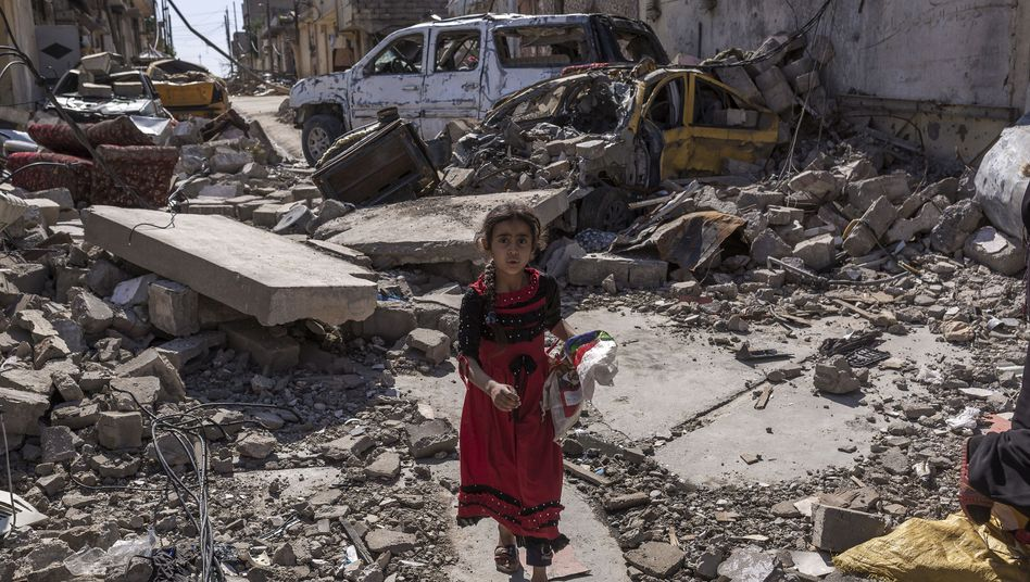 A girl walks through the destroyed streets of Mosul.