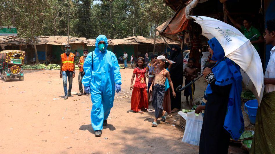 Mitarbeiter einer Hilfsorganisation im Schutzanzug im Flüchtlingslager in Cox's Bazar