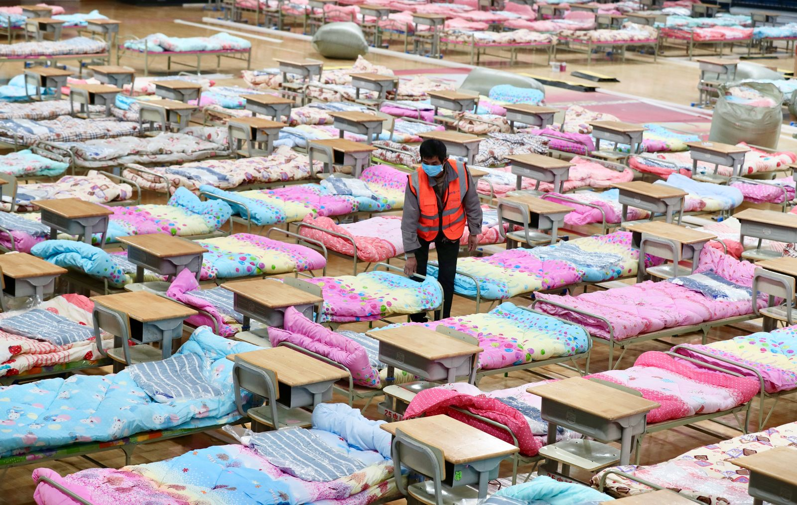 Worker sets up beds at the Hongshan Stadium to convert it into a makeshift hospital following an outbreak of the new coronavirus, in Wuhan