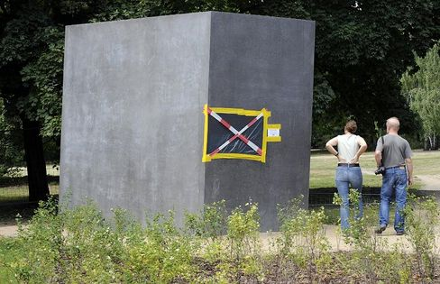Visitors inspect damage done to the monument to homosexuals persecuted by the Nazis in Berlin.