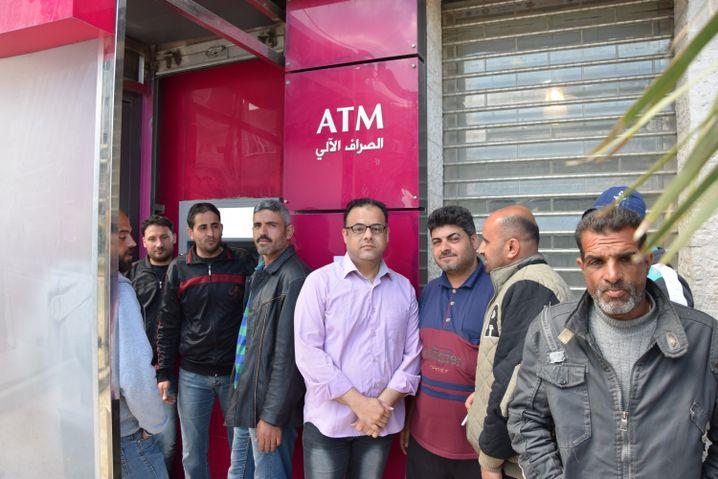 Abu Ali (Hemd und Brille) wartet mit Anderen vor einer Bank in Dschabalija