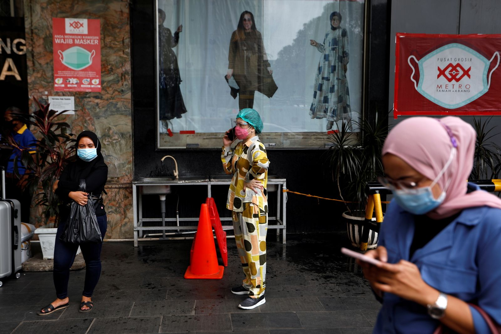 Women wearing protective masks following the outbreak of the coronavirus disease (COVID-19) stand outside a shopping mall at Tanah Abang textile market in Jakarta
