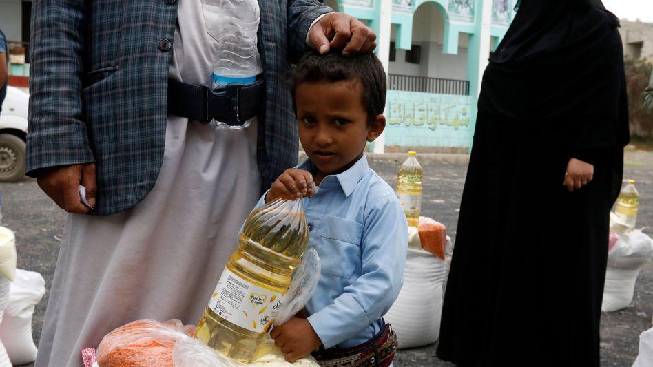 Ein Junge und sein Vater warten in Sanaa im Jemen an einer Lebensmittelausgabe