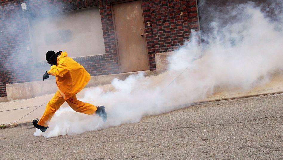 Proteste: Ein Demonstrant versucht eine Nebelgranate der Polizei wegzuschießen