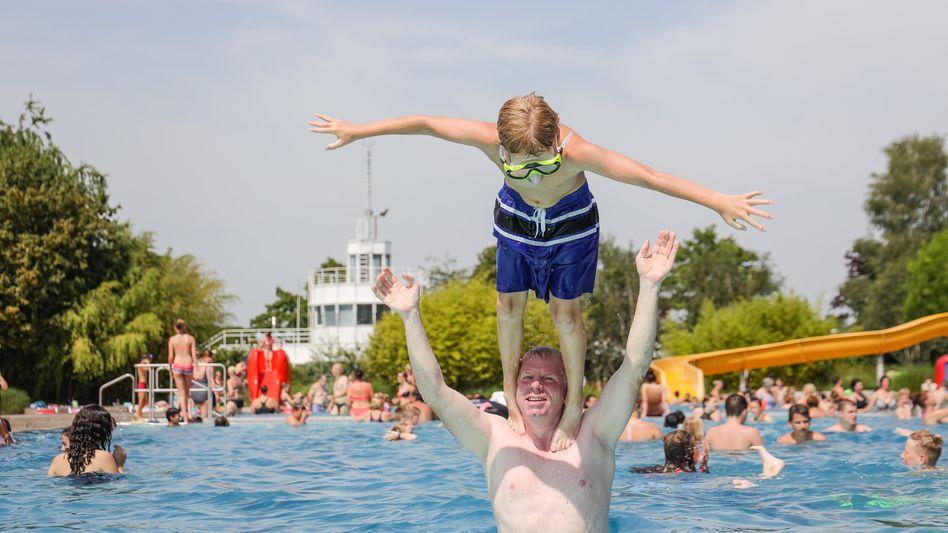Hitze in Lingen: Max und sein Vater Martin spielen zusammen im Schwimmbad, im Hintergrund ist die Wetterwarte des Deutschen Wetterdienstes (DWD) zu erkennen