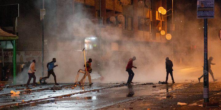 Demonstranten laufen in Johannesburg weg, nachdem die Polizei Tränengas eingesetzt hat