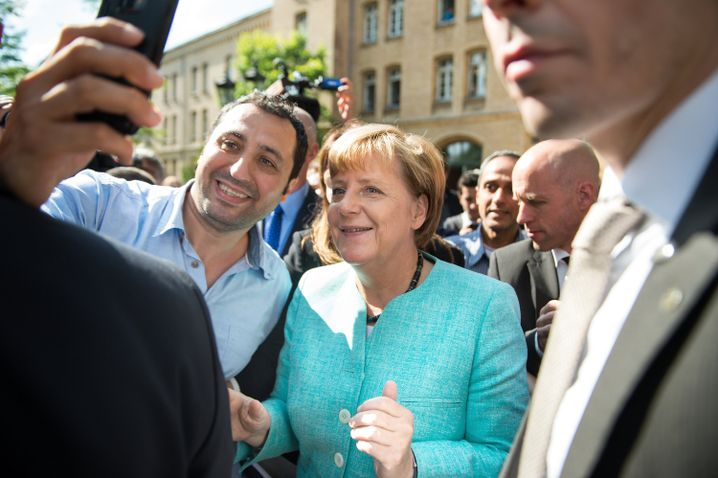 Chancellor Angela Merkel takes a selfie with Hassan Alasad in Berlin on Sept. 10, 2015 in Berlin.