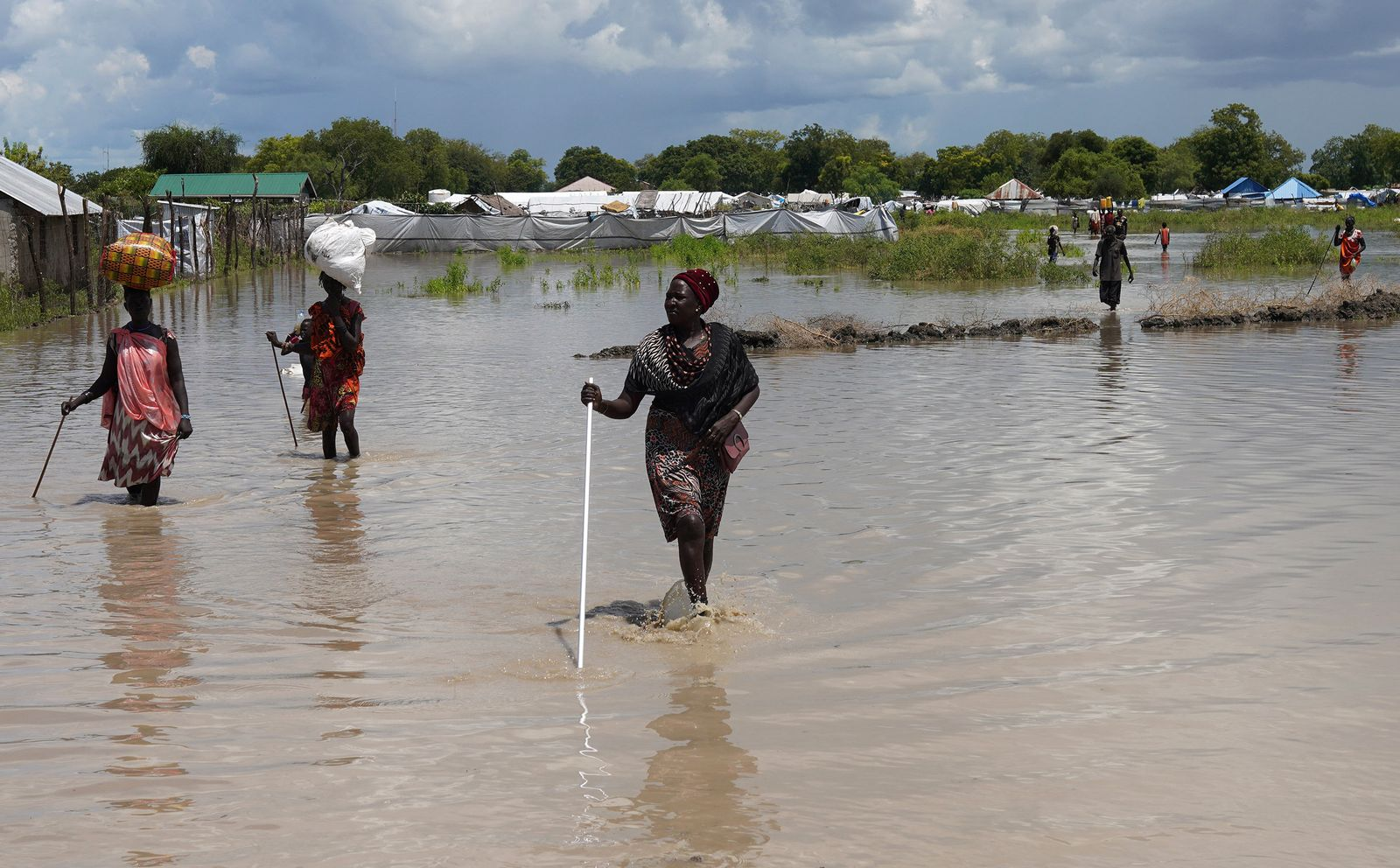 Women wade through flood waters after the River Nile broke the dykes in Pibor