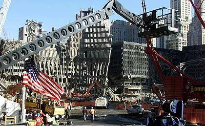 Sternenbanner im Trümmerfeld - Im Hintergrund das Gerippe der Eingangshalle von einem der Türme des World Trade Centers.