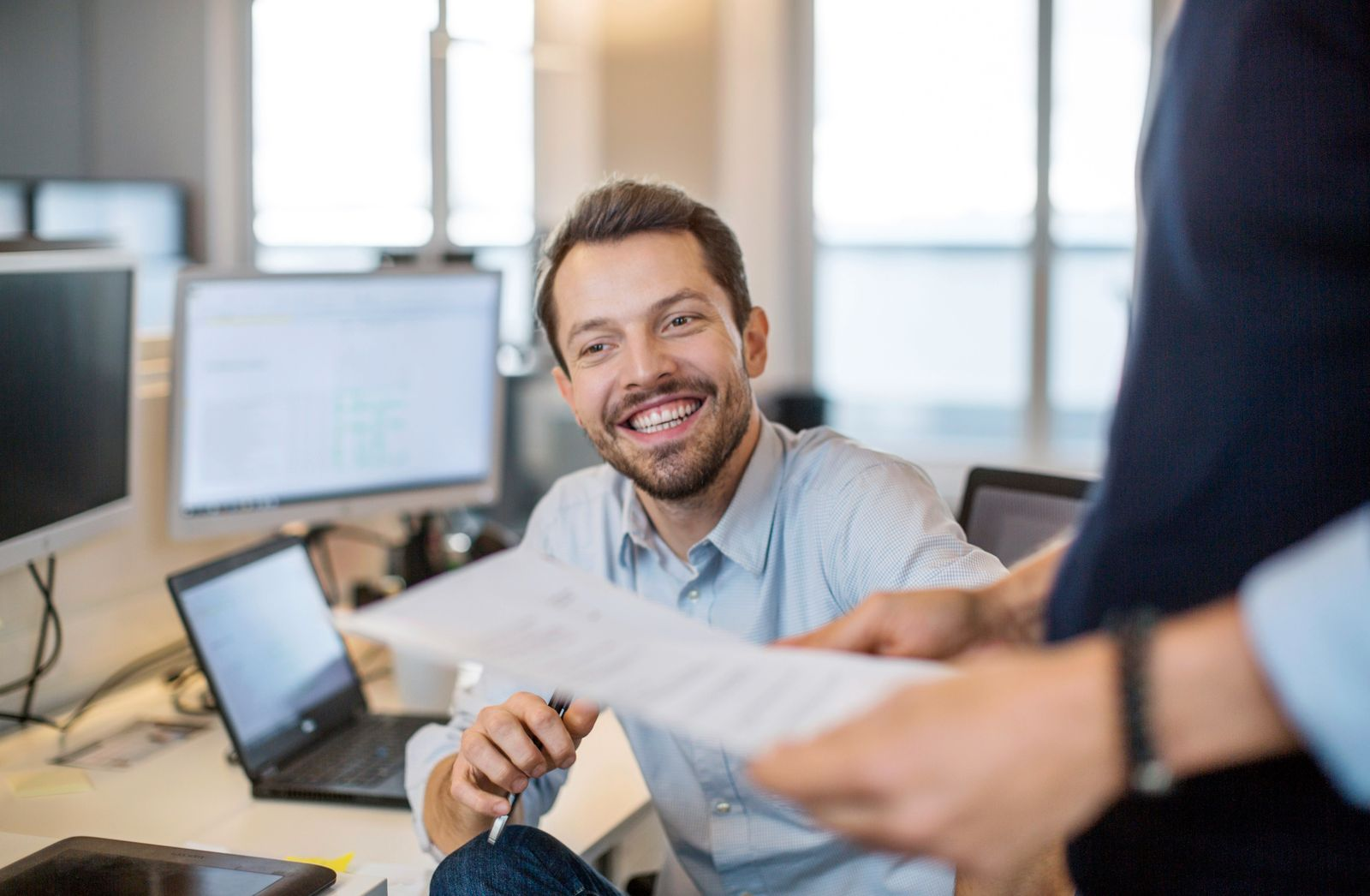 Young businessman sitting at his desk and smiling