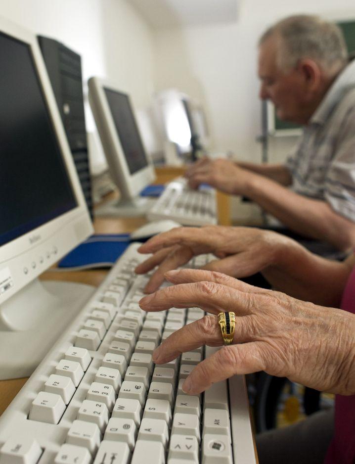 """Senioren beim Seniorenkurs """"IBAN-Eingabe für Senioren an schwarzen Bildschirmen"""""""