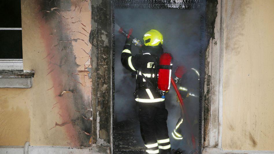 Ein Feuerwehrmann löscht im Inneren des brennenden Amtshauses. Bei dem Feuer wurden Teile des Gebäudes zerstört, in dem auch die Ausländerbehörde und das Jobcenter der Stadtverwaltung untergebracht sind