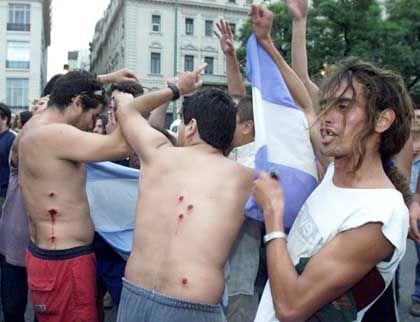 Feiernde Verwundete: Diese Demonstranten bejubelten den Rücktritt von Präsident Fernando de la Rúa und zeigten zugleich ihre Verletzungen. Die Wunden stammen von Gummigeschossen der Polizei