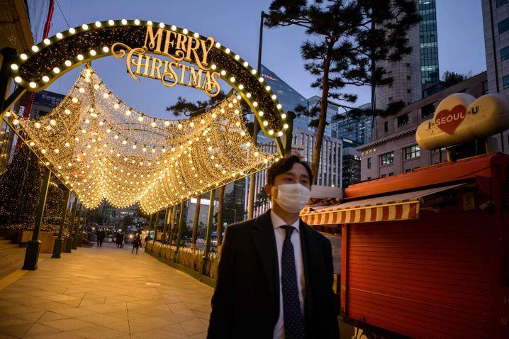 Ein Mann mit Maske geht an Weihnachtsdeko in Seoul vorbei