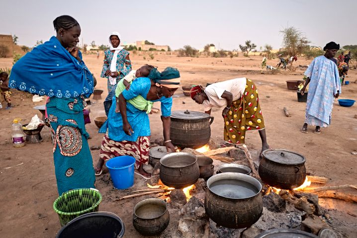 Displaced women in Mali preparing food. The coronavirus will worsen the suffering already being experienced by many people.