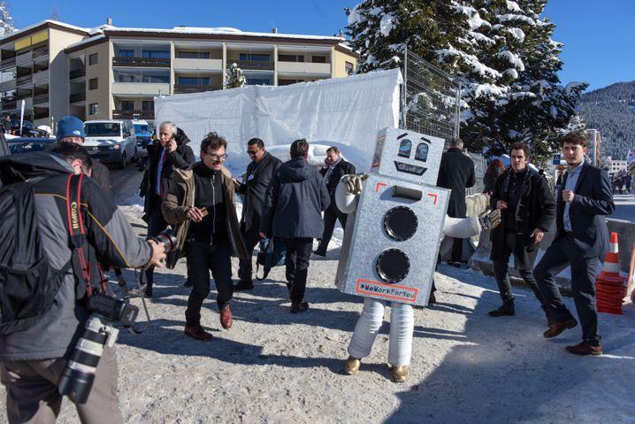 Januar 2016: Aktion der Initiative beim Weltwirtschaftsforum in Davos. Freundliche Roboter übernehmen die Arbeit - und finanzieren das Grundeinkommen?