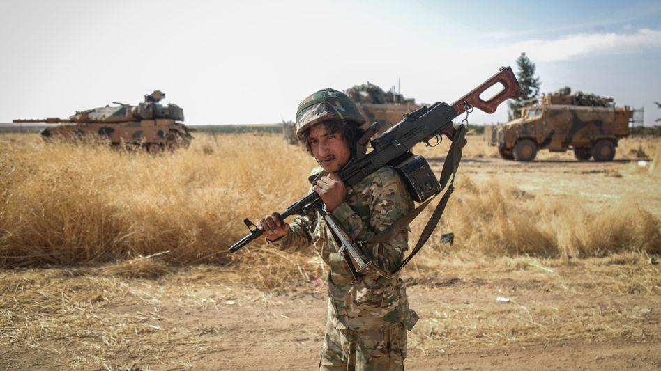 Von der Türkei unterstützter Rebell der Syrischen Nationalarmee, im Hintergrund türkische Panzer