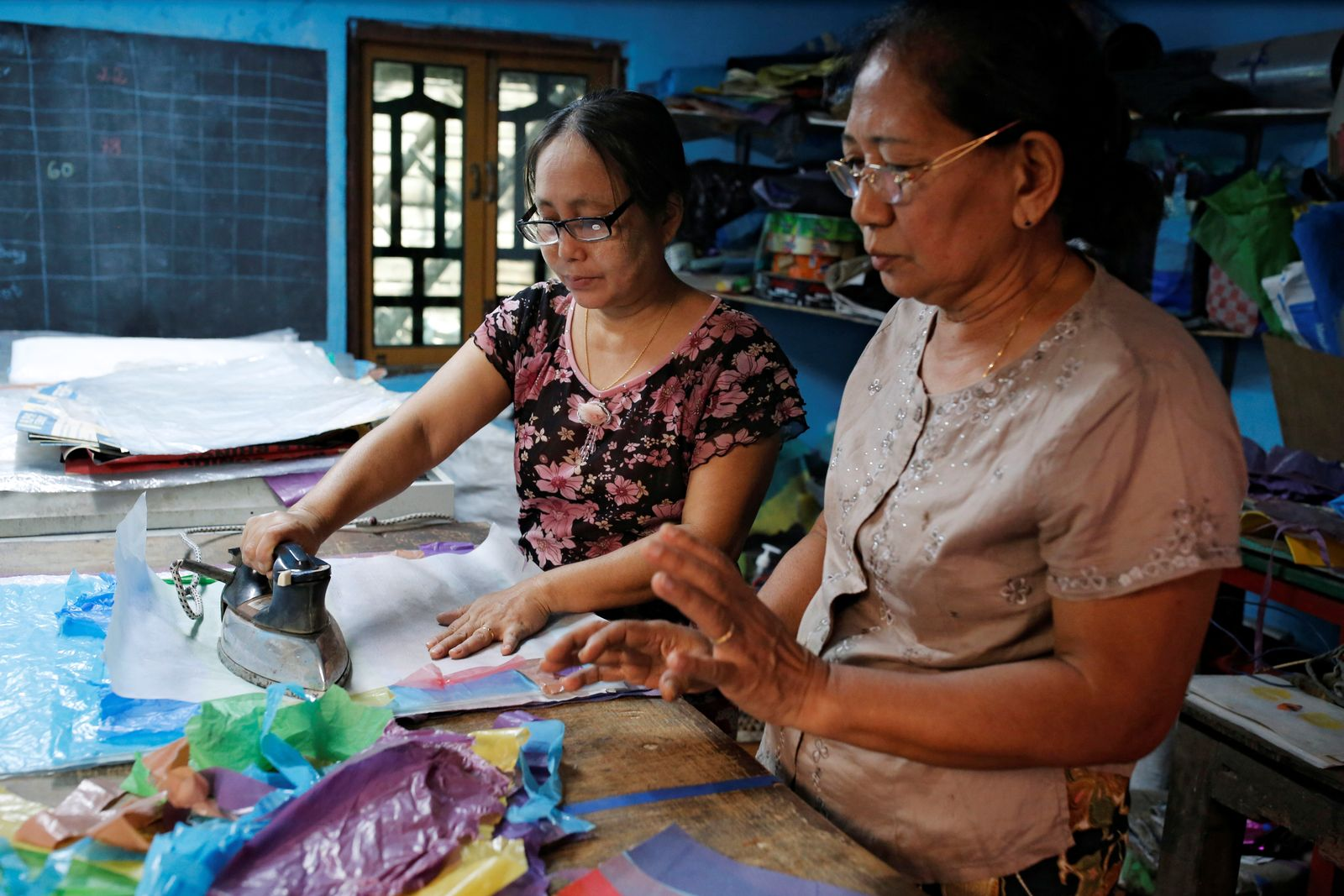 Wendy and Hla Hla Nwe use recycled plastic waste to make various products at the shop Chuchu House in Dalla township, Yangon