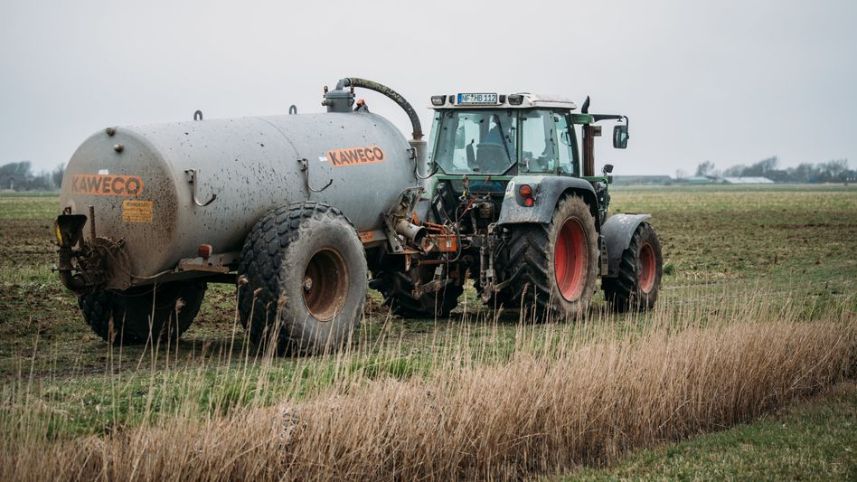 Ein Landwirt fährt Gülle auf einem Feld aus (Archivbild)