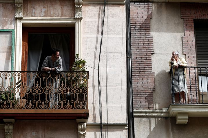 Neighbors in Madrid communicate with one another over their balconies.