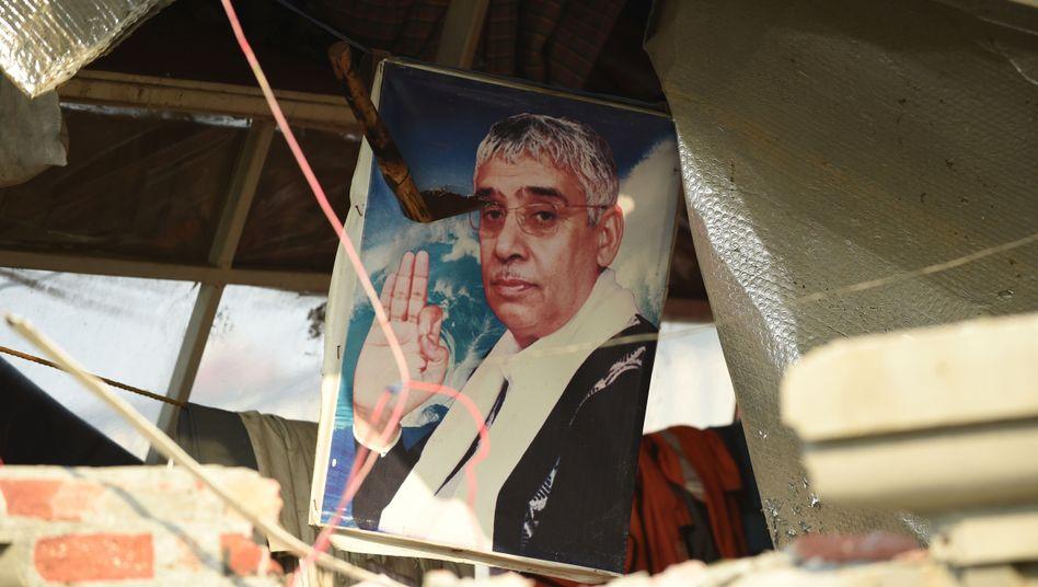 Porträt von Guru Baba Rampal am verwüsteten Eingang des Ashram: heftige Krawalle