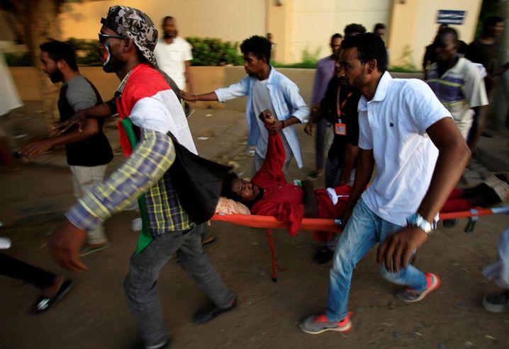 Zivilisten tragen einen verwundeten Demonstranten durch die sudanesischen Hauptstadt Khartum