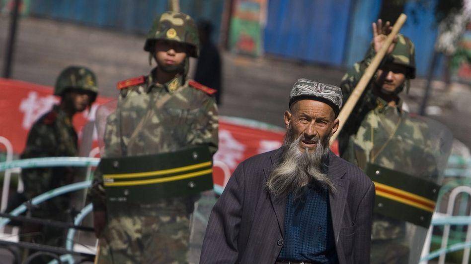 Angehöriger der uigurischen Minderheit in der Provinz Xinjiang mit chinesischen Sicherheitskräften