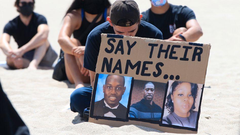 Ein Demonstrant in Los Angeles hält ein Schild mit den Gesichtern der getöteten Ahmaud Arbery, George Floyd und Breonna Taylor