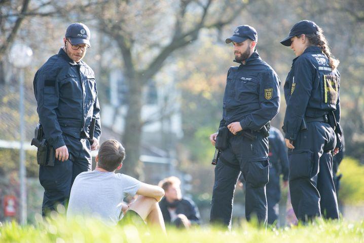 Polizeikontrolle in einem Stuttgarter Park am 19. März: Treffen sich mehr Menschen als erlaubt, werden hier zwischen 100 und 1000 Euro fällig